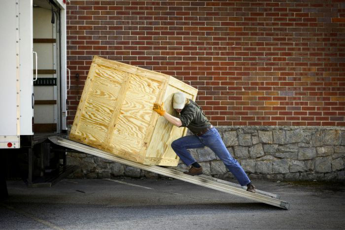 Man pushing large wooden box up ramp into box truck